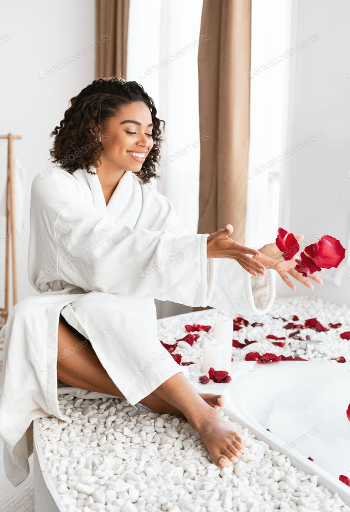 Delightful afro girl throwing rose petals into foamy bath