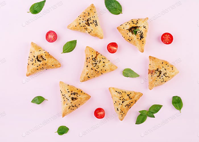 Asian food. Samsa (samosa) with chicken fillet and green herbs on pink background. Top view