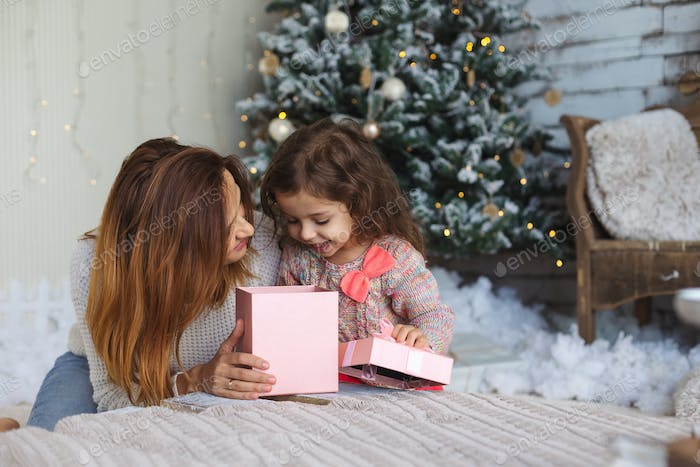 Happy mom with kid looking inside of magic Christmas gift box