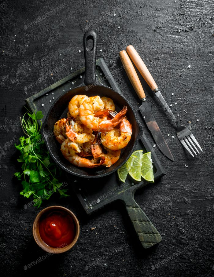 Fried shrimps in a frying pan on a cutting Board with sauce, parsley and slices of lime.