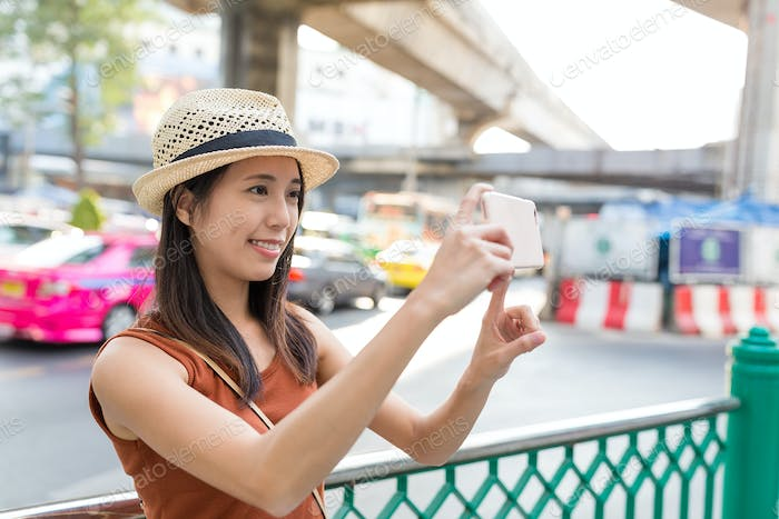 Woman taking photo on cellphone in Bangkok city
