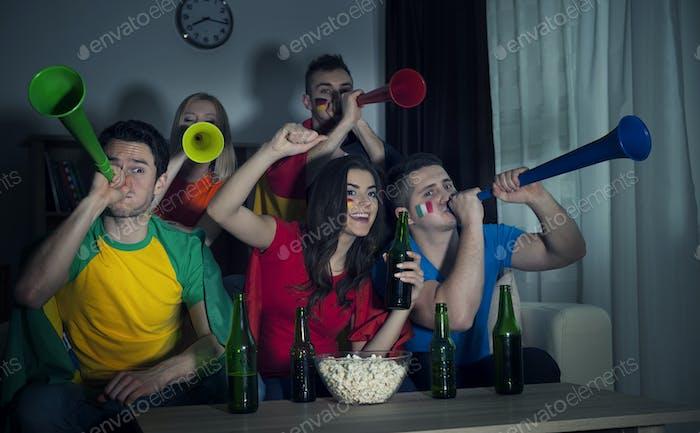 Multinationale Freunde jubeln Fußballspiel zu Hause