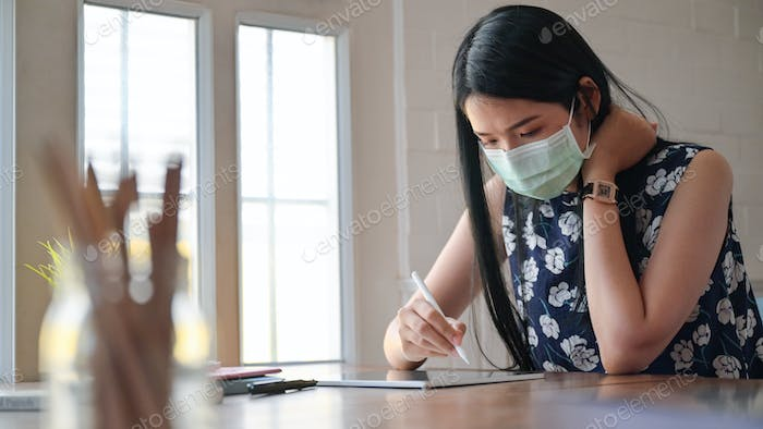 Asian women work at home to prevent the spread of the coronary virus, or Covid-19.