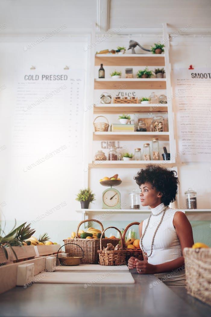 Young woman behind juice bar counter
