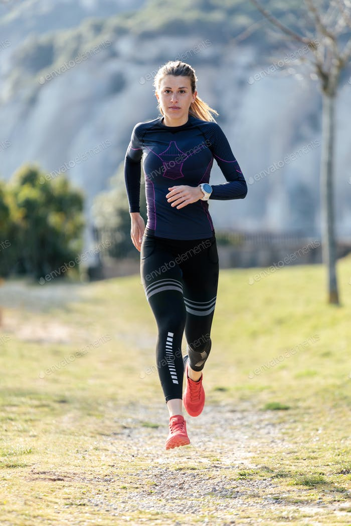 Sporty young woman running on mountain in beautiful nature.