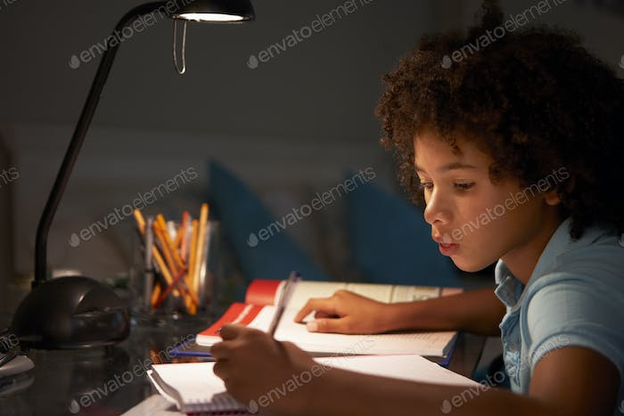 Young Boy Studying At Desk In Bedroom In Evening