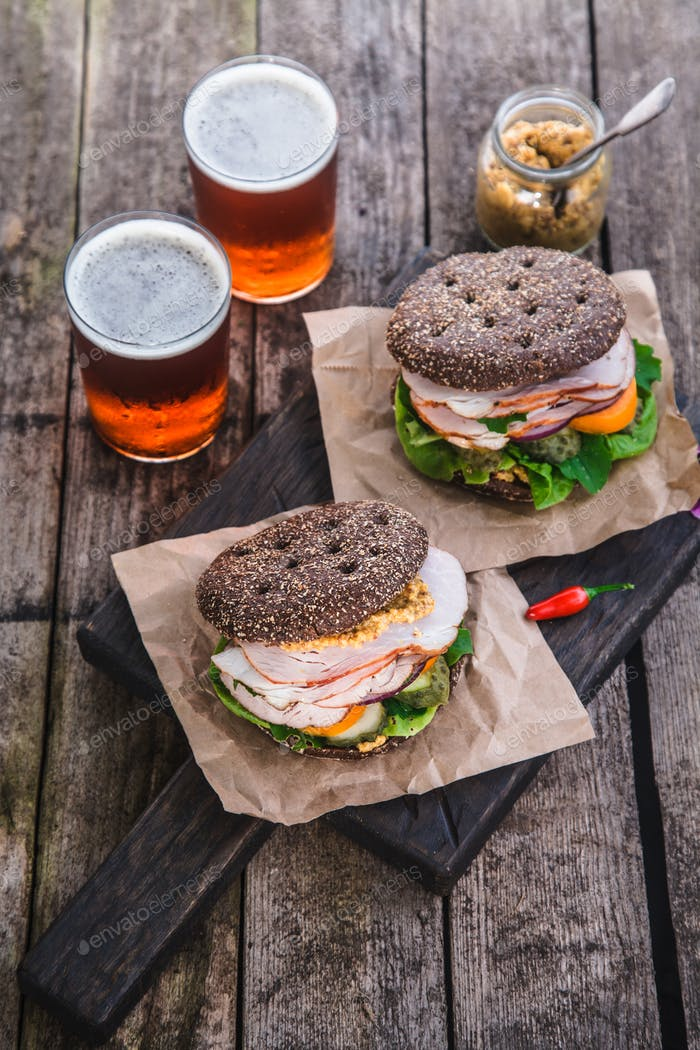 Homemade sandwich with ham and a glass of beer on an old background, top view