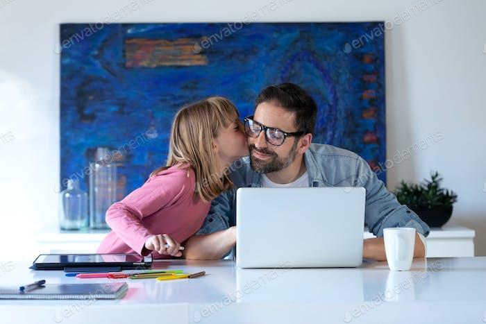 Hübsches kleines Mädchen küsst ihren Vater, während er mit Laptop zu Hause arbeitet.