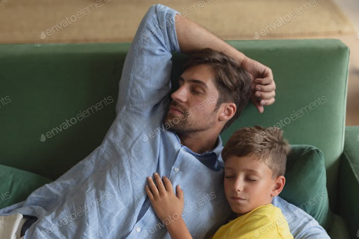 Front view of Caucasian father and son sleeping together on a sofa in living room at home