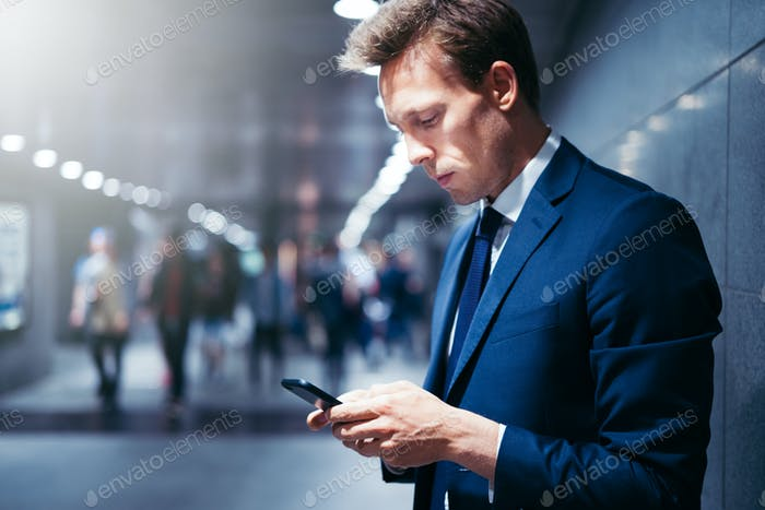 Young executive waiting for a subway train reading text messages