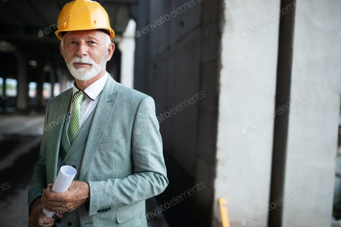 Smiling construction manager, engineer, businessman, architect standing on construction site