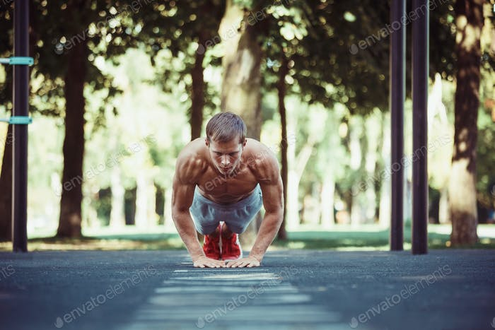 Athlete doing exercises at stadium at park