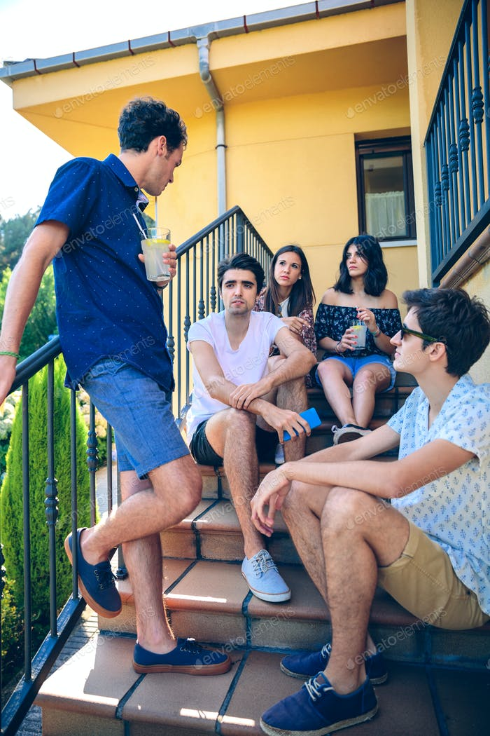 Young people talking outdoors sitting on home stairs steps