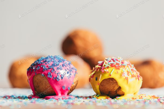 Two decorated doughnuts laying on a table.