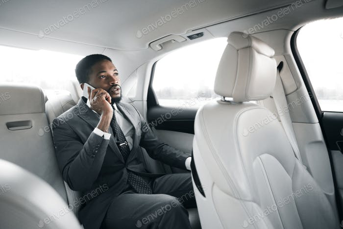 Businessman Talking On Phone Sitting On Back Seat In Car