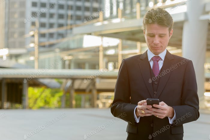 Businessman using mobile phone in front of modern building at Ba