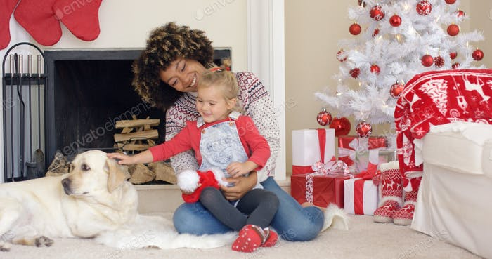 Happy mother and child with dog on Christmas Day