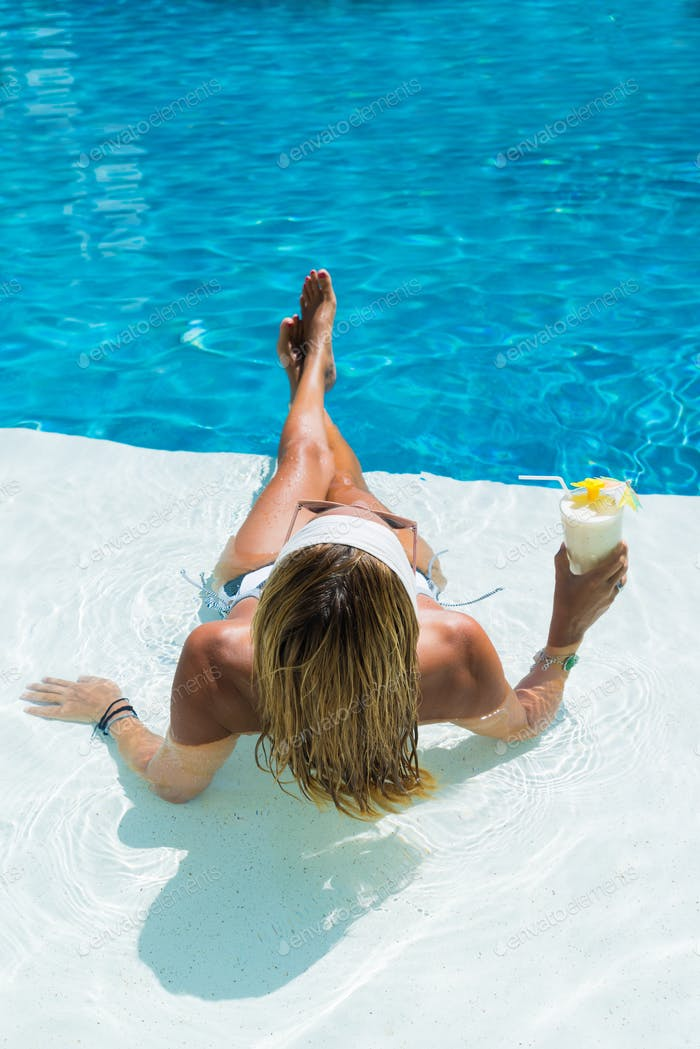 WOman at the swimming pool with a pina colada cocktail