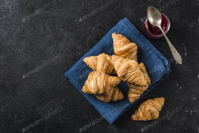Freshly baked French croissants with a jar of jam on a black background with a dark blue napkin.