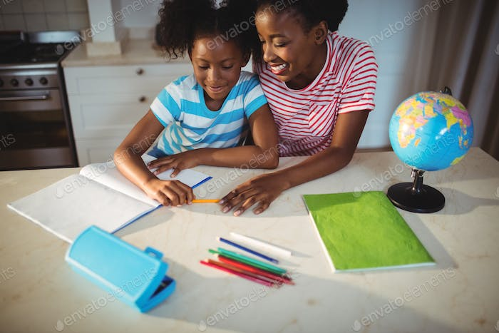 Mother assisting daughter with homework