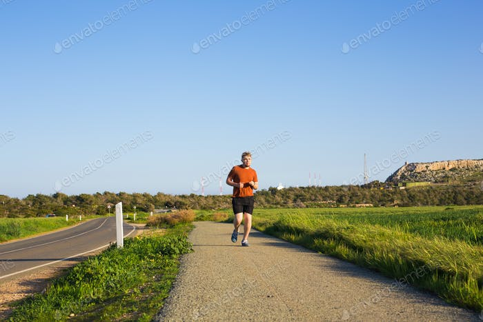 Portrait of a sporty young man running outdoors in nature