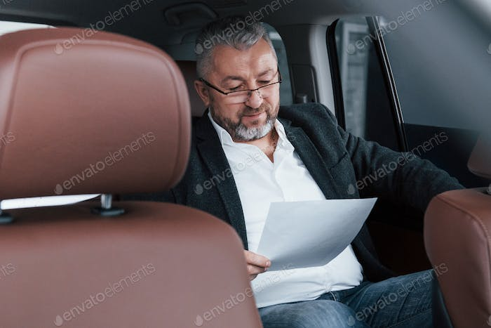 Paperwork on the back seat of the car. Senior businessman with documents