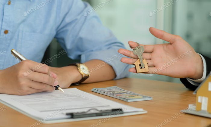Close-up shot of Homebuyers signing home contracts and house brokers holding house key.