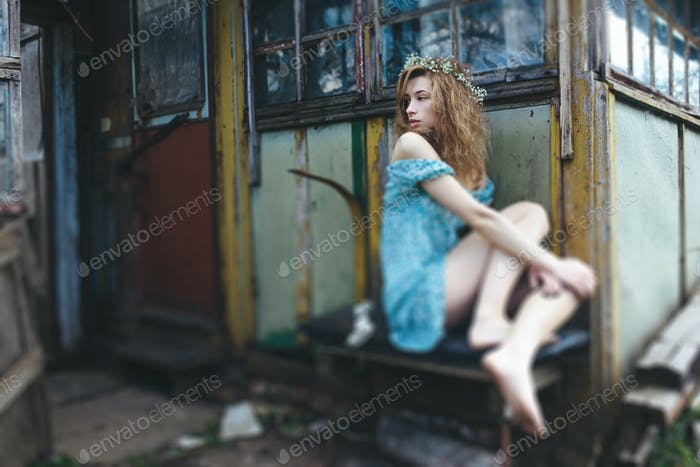 young and beautiful girl sitting at the door