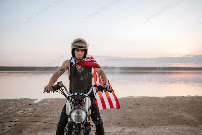 Man in golden helmet and american flag cape driving motorcycle