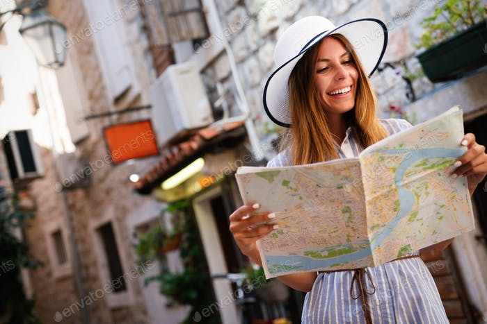 Young female tourist with map looking for a way on summer vacation