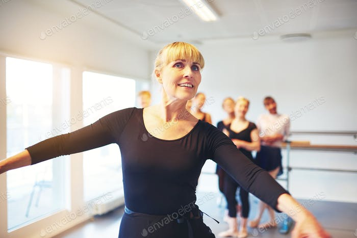 Mature woman doing ballet in a dance studio