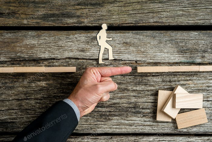 Businessman supporting paper cut out of a man walking forwards t