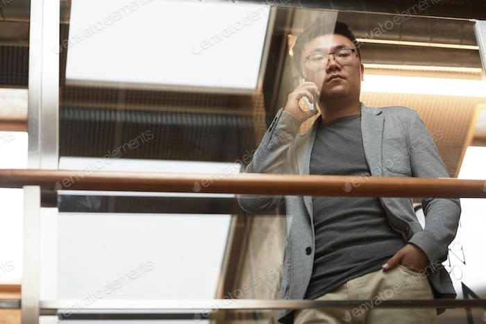 Asian Businessman Speaking by Smartphone Low Angle