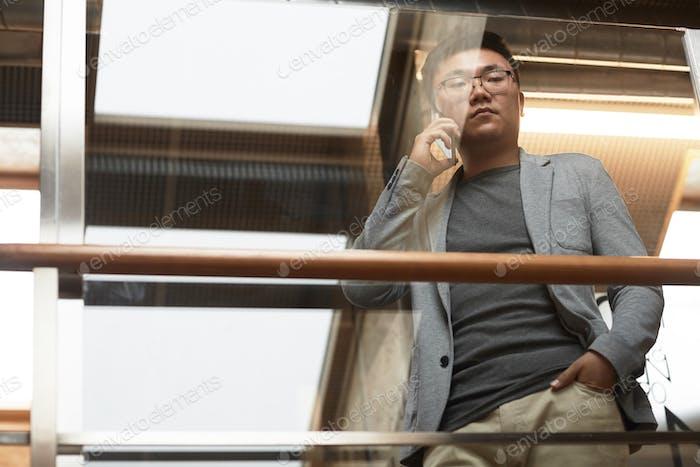 Asiatische Geschäftsmann sprechen durch Smartphone Low Angle