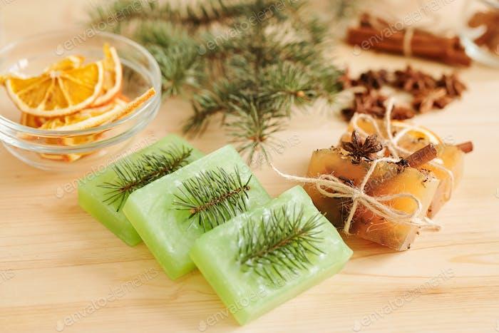 Frische handgemachte Seifenriegel duftet von Nadelbäumen und aromatischen Gewürzen auf dem Tisch