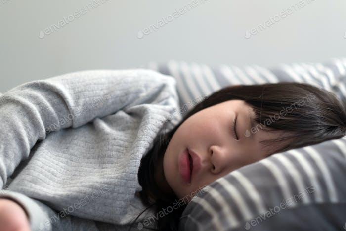 Child girl sleeping on bed
