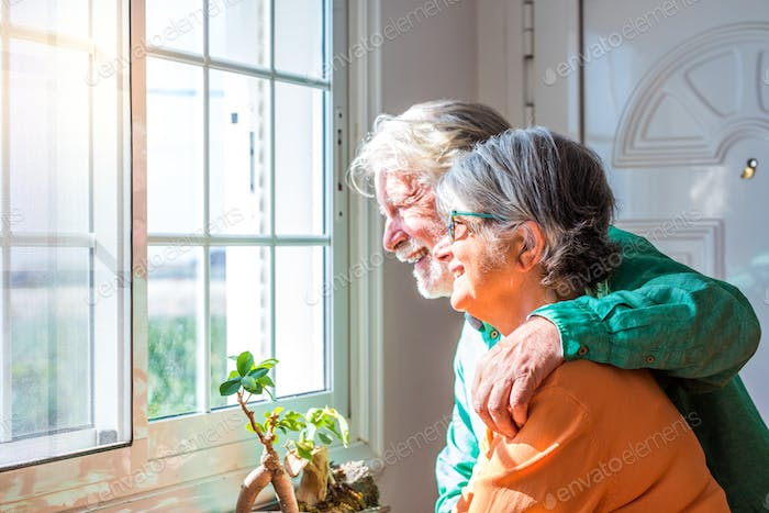 couple of two cute old and mature people or seniors having fun together at home looking outside