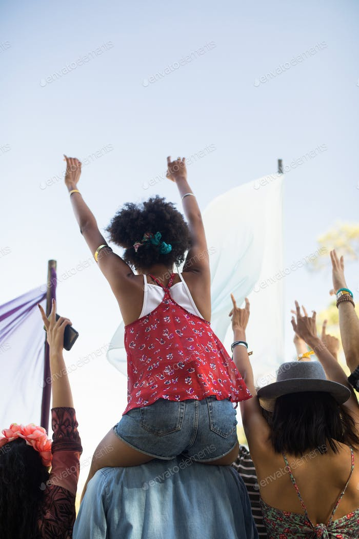Friends enjoying against sky at music festival