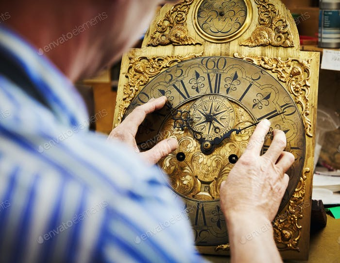 A clock maker working on antique clock