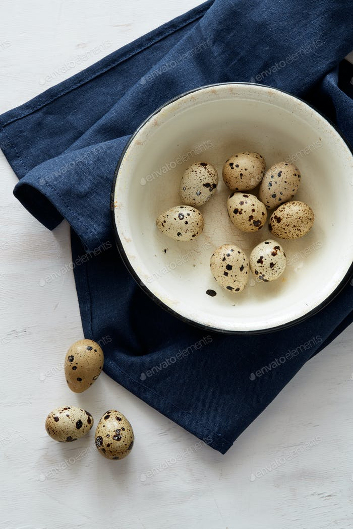 Flatview of some quail eggs in white bowl on blue linen fablic b