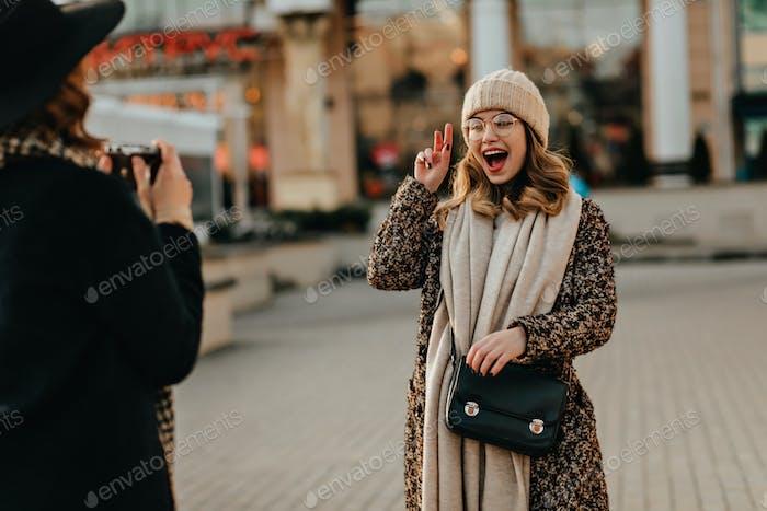 Mädchen im langen Schal posiert vor Aufregung auf der Straße. Außenaufnahme einer lächelnden Dame, die her