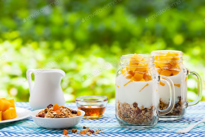 Healthy Breakfast, Dessert. Fresh Mango Fruit with Yogurt and Granola in Jars. Outdoor Background.