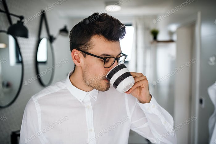 Young man with white shirt in the bathroom in the morning, drinking coffee