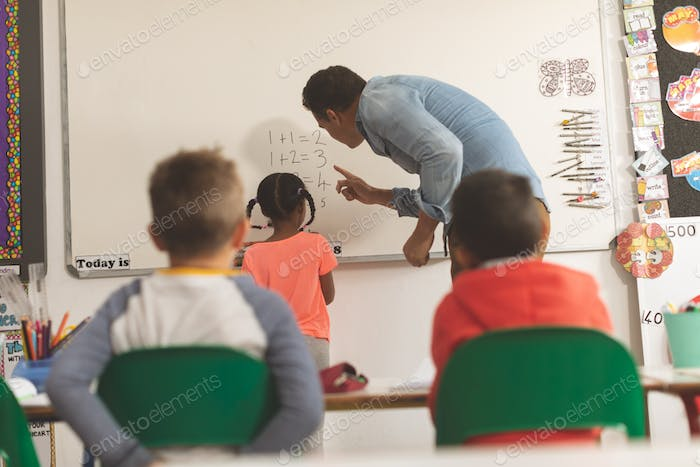Caucasian teacher teaching mathematics to one of his school kid on a whiteboard