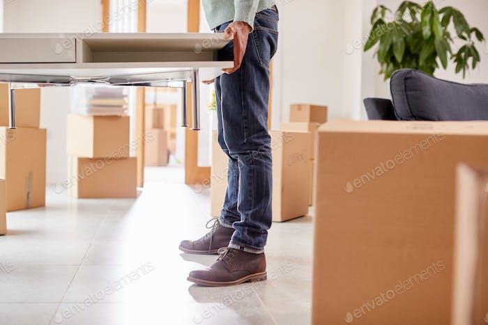 Nahaufnahme des paares in neue zuhause auf bewegten tag tragen tisch zusammen
