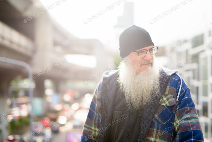 Mature handsome bearded man thinking against view of the city streets