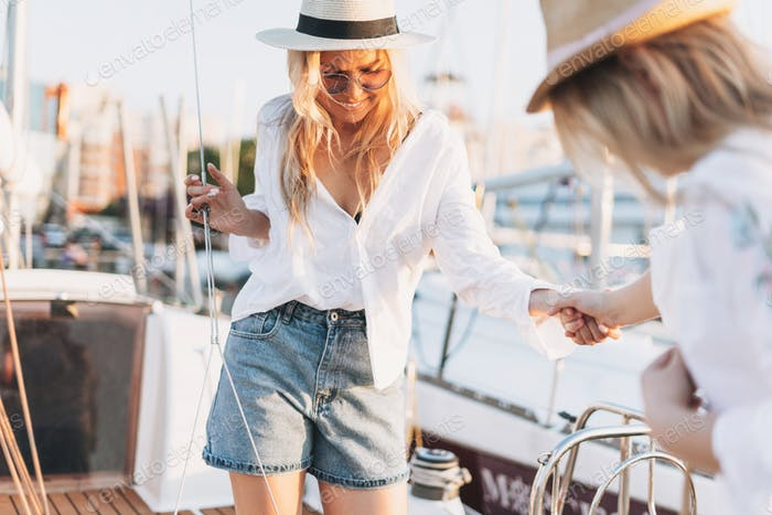Two beautiful blonde girls friends mother and daughter in white and straw hats on yacht at pier