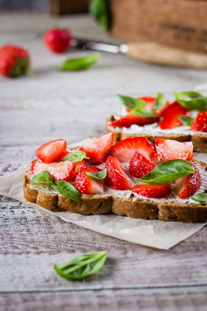 Strawberry bruschetta with cottage cheese,basil and strawberry on baking paper