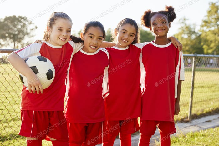 Four young girls in football strip looking to camera smiling
