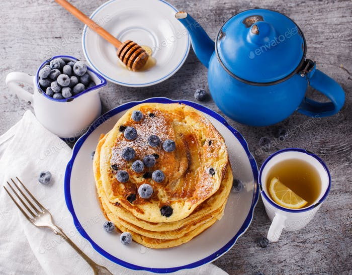 Pancake with banana , blueberries and honey.